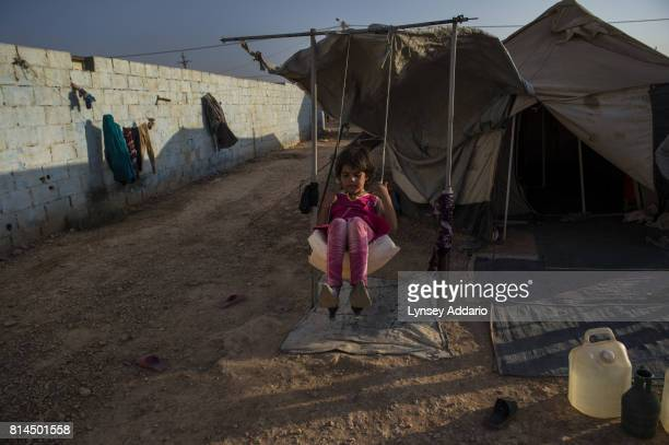 A girl plays on a makeshift swing in Zaatari camp in Mafraq Province Jordan September 14 2013 There are roughly 120000 Syrian refugees living in the...