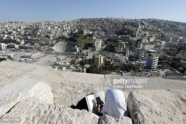 A girl plays on her phone as she sits on the ramparts of Amman's Citadel overlooking the Roman Theater in the Jordanian capital on March 14 2015 AFP...