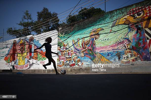 A girl plays soccer in front of graffiti created by acclaimed local graffiti artist Acme in the pacified PavaoPavaozinho community on May 8 2014 in...