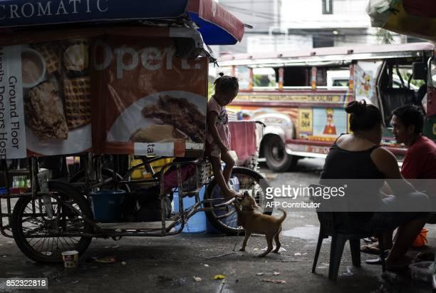 A girl plays with a dog along a street in Manila on September 23 2017 President Rodrigo Duterte's deadly drug war and armed Islamist rebellion pose...