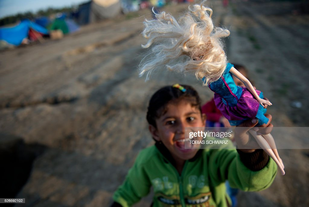 A girl plays with a doll at a makeshift camp for migrants and refugees near the village of Idomeni not far from the Greek-Macedonian border on April 30, 2016. Some 54,000 people, many of them fleeing the war in Syria, have been stranded on Greek territory since the closure of the migrant route through the Balkans in February. / AFP / TOBIAS