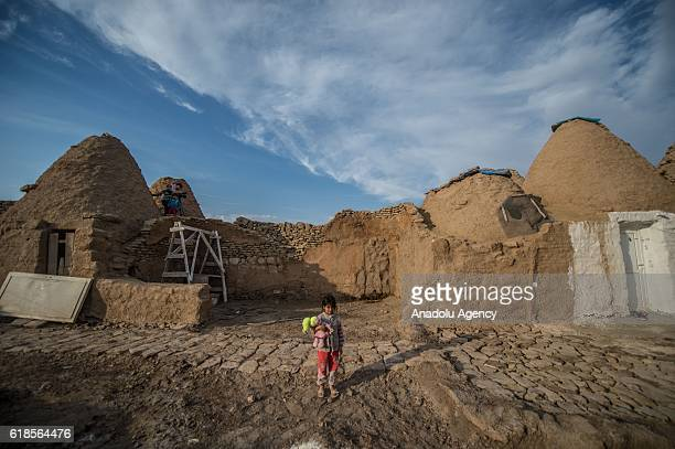 A girl plays with a doll near the conical domed houses in the Harran district of Sanliurfa a province in southeastern Turkey on October 27 2016...