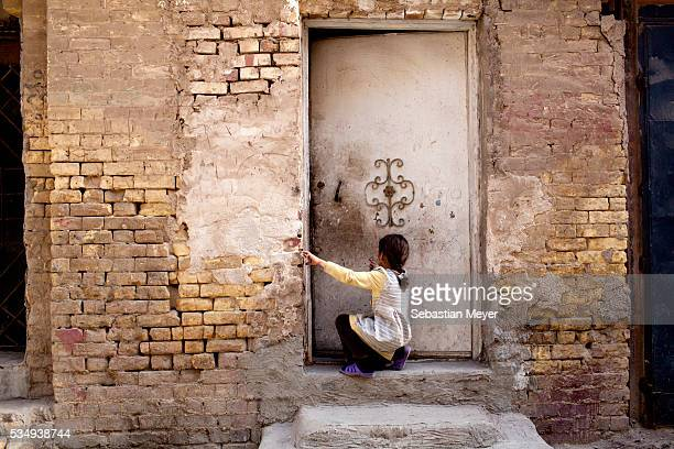 A girl plays with a door of a house in the Kadhmiya district of Baghdad 10 years after the US led invasion Iraq continues to suffer from violence and...
