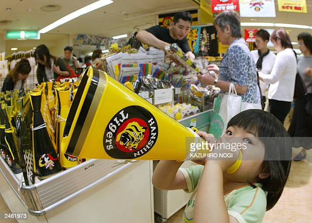 A girl plays with a megaphone to cheer the Hanshin Tigers currently atop the Japanese Central League baseball at a Tigers' goods floor in the Hanshin...