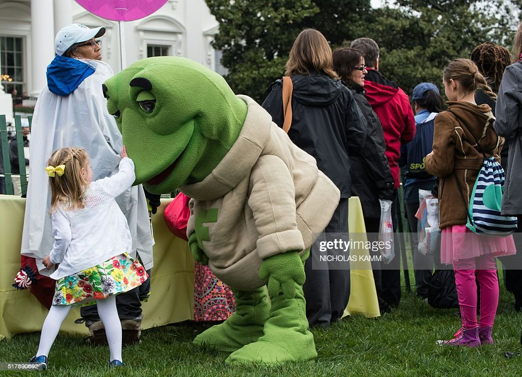 A girl plays with a person dressed as a frog at the annual Easter Egg Roll at the White House in Washington DC on March 28 2016 / AFP / Nicholas Kamm