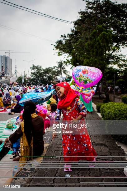 A girl plays with her balloon after the Eid ElFitr pray on July 28 2014 in Jakarta Indonesia Eid AlFitr marks the end of Ramadan the Islamic month of...