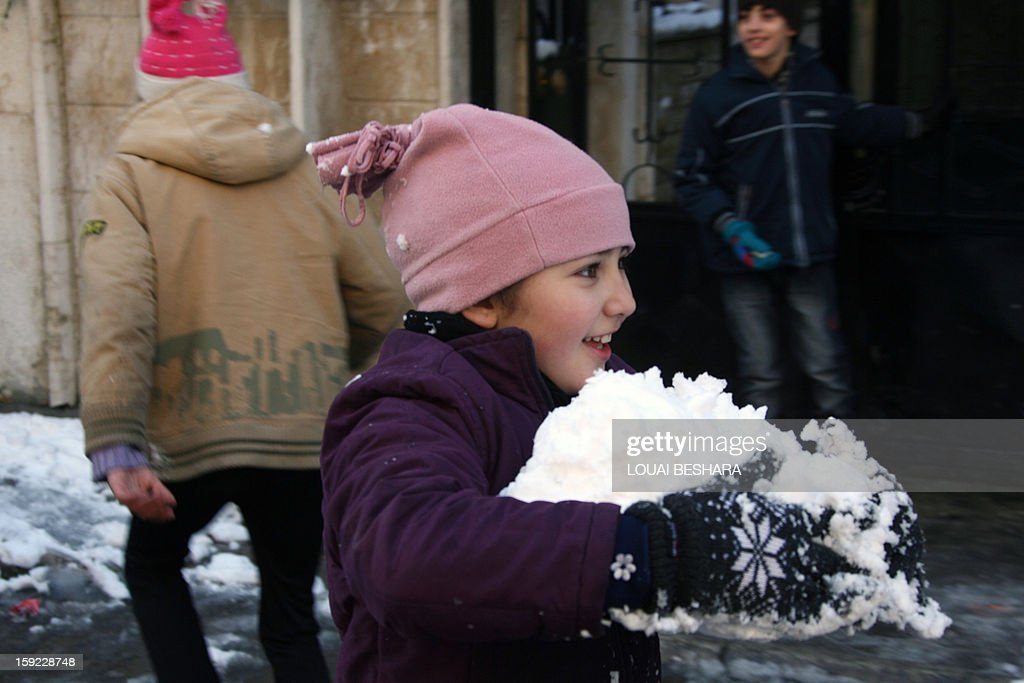 A girl plays with snow on January 10, 2013 in the Syrian capital of Damascus after heavy snow falls. Snow carpeted Syria's war-torn cities but sparked no let-up in the fighting, instead heaping fresh misery on a civilian population already enduring a chronic shortage of heating fuel and daily power cuts.