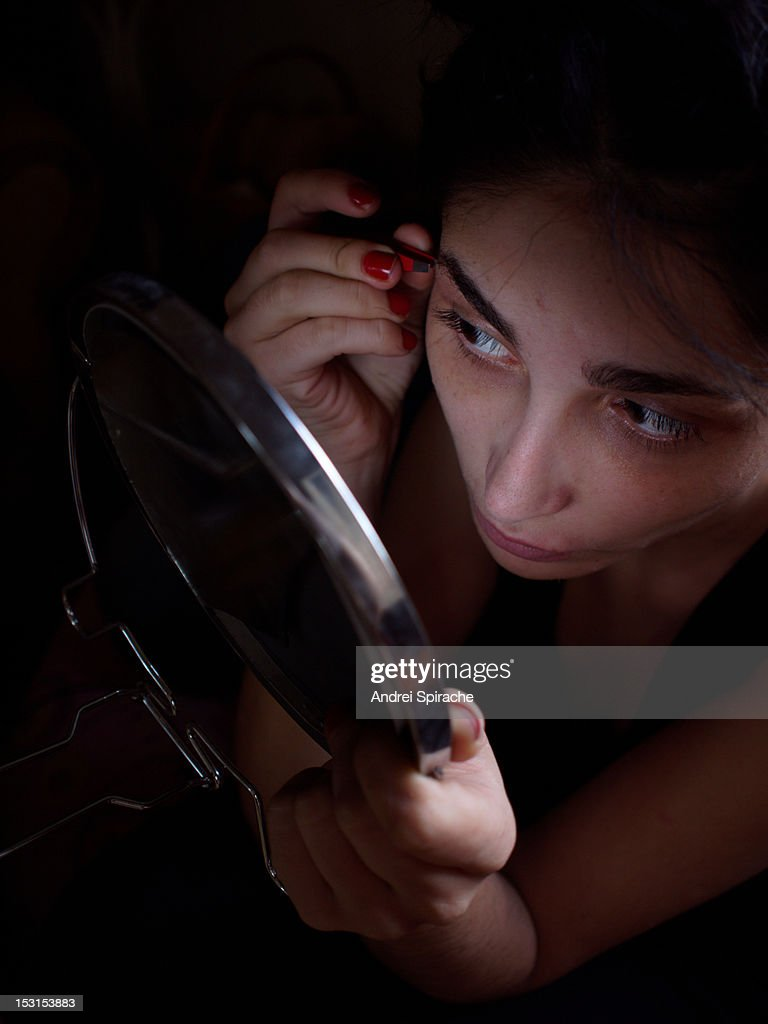 Girl plucking her eyebrows in the mirror : Stock Photo