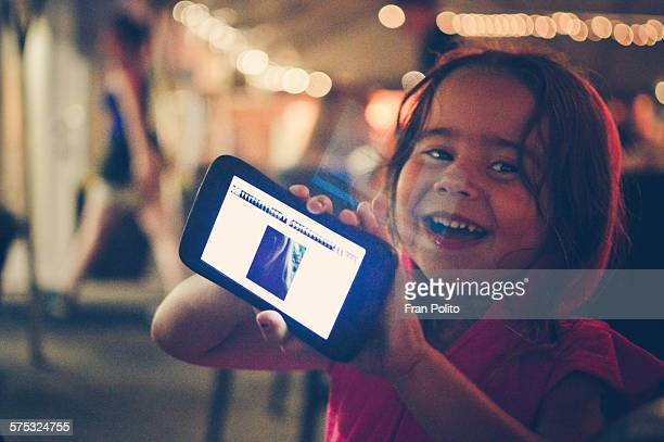 A girl pointing a smart phone at the camera
