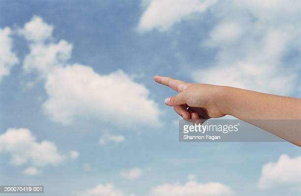 Girl (8-10) pointing at clouds, close up