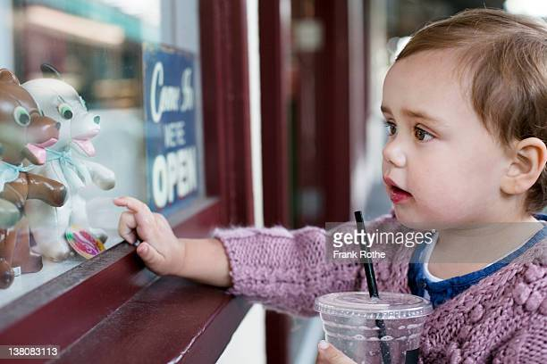girl pointing at toys in shopping window
