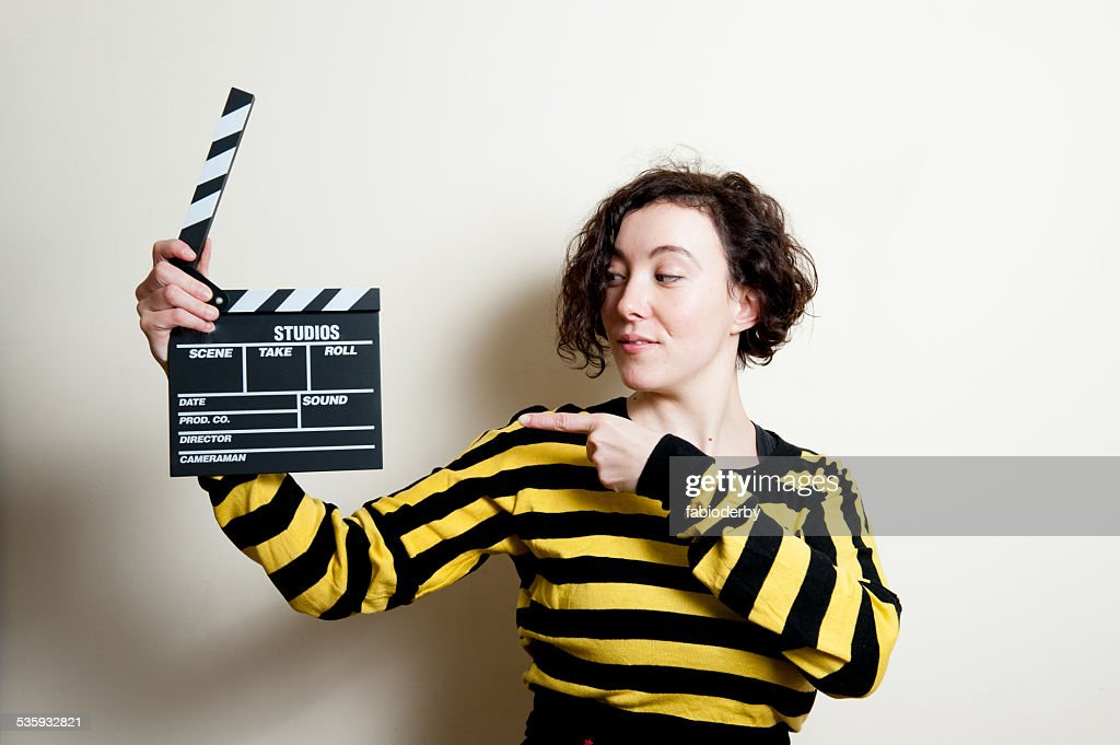Girl pointing out movie clapper on white background : Stock Photo