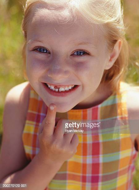 Girl (6-7) pointing to missing tooth, portrait, close-up