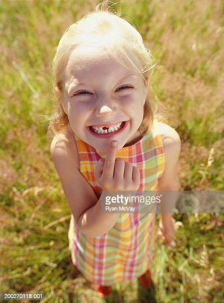 Girl (6-7) pointing to missing tooth, portrait