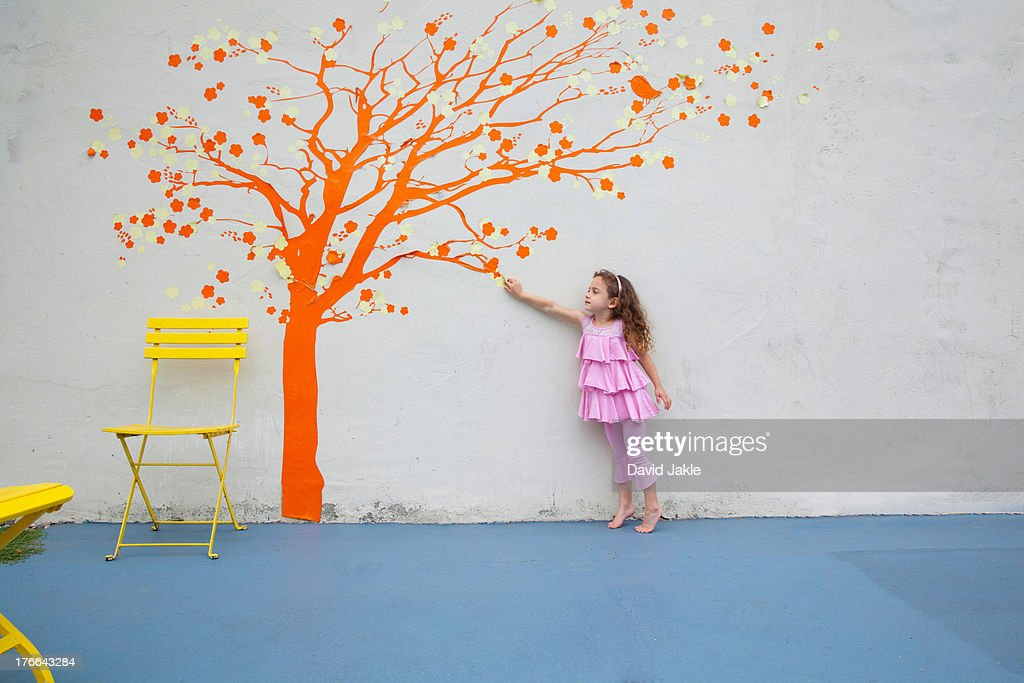Girl pointing to orange tree mural on wall
