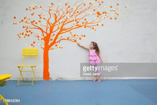 Girl pointing to orange tree mural on wall : Stock Photo