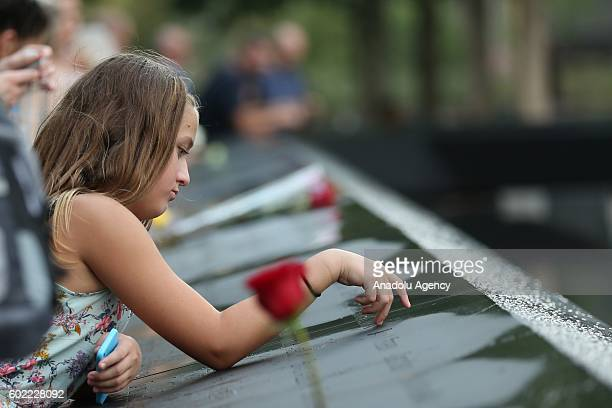 A girl points her finger on a victim's name as people visit the National 11 September memorial a day before the 15th anniversary of the 9/11 attacks...