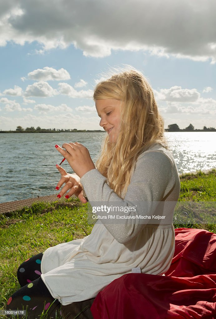 Girl polishing her nails in grass : Stock Photo