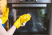 Close up of female hand with yellow protective gloves cleaning oven door. young smiling woman in protective glove with rag cleaning oven. Girl polishing kitchen. People, housework, housekeeping, clean