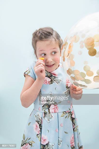 Girl popping confetti balloon with pin