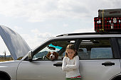 Girl (6-8 years), portrait, standing beside car with bonnet open