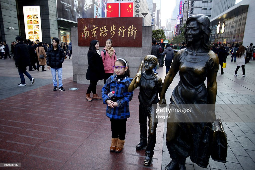 A girl poses for a photo with a sculpture in Nanjing Road Walking Street on February 3, 2013 in Shanghai, China.