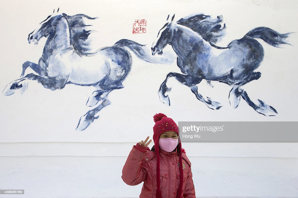 A girl poses for a photograph beside a snow sculpture depicting horses at the 26th Harbin International Snow Sculpture Art Expo in Sun Island park on December 22, 2013 in Harbin, China. The Harbin International Ice and Snow Sculpture Festival is one of the largest ice and snow festivals in the world and is a popular winter destination for both Chinese and foreign visitors.