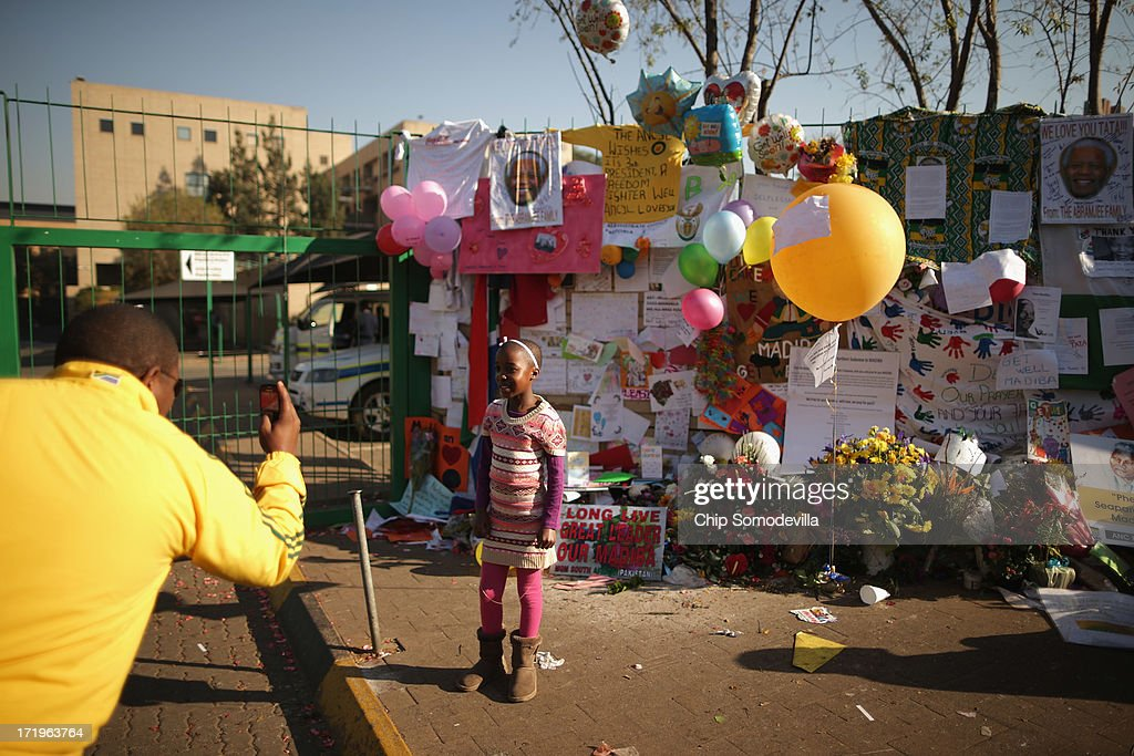A girl poses for a photograph in front of a wall covered with messages of thanks and hope for former South African President Nelson Mandela at the at the Mediclinic Heart Hospital where he is being treated for a recurring lung infection June 30, 2013 in Pretoria, South Africa. The anti-apartheid icon and Nobel Peace Prize laureate has been in the hospital for three weeks where his condition has been described as 'critical but stable.'