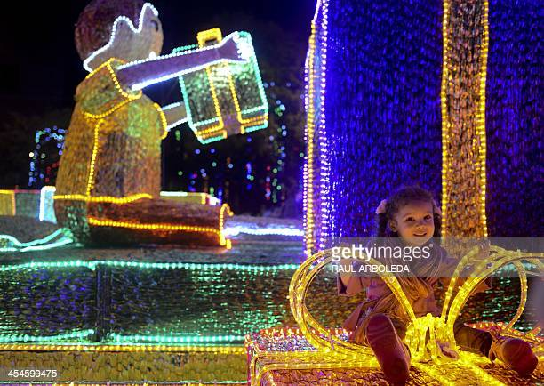 A girl poses for a picture at the Christmas lights illumination along the Medellin river on December 9 2013 in Medellin Antioquia department Colombia...