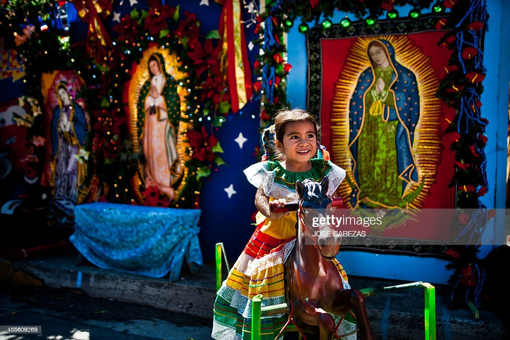 A girl poses for a picture in a makeshift photo studio outside the Basilica de Guadalupe church in San Salvador El Salvador on December 12 2014...