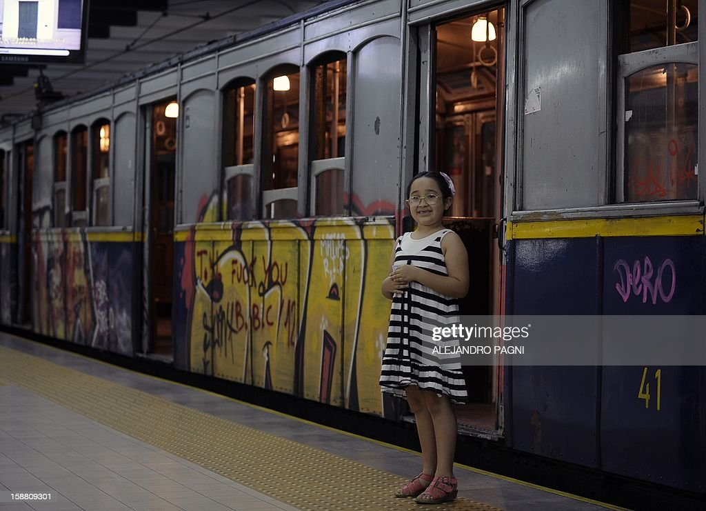 A girl poses for a picture next to one of the historic wagons of La Brugeoise of the subway Line A which is expected to be close soon following a decision by city mayor Mauricio Macri to replace the fleet with Chinese-made wagons, in Buenos Aires, on December 29, 2012. Line A was the first subway line to work in the southern hemisphere and its trains are among the ten oldest still working daily. The La Brugeoise wagons were constructed between 1912 and 1919 by La Brugeoise et Nicaise et Delcuve in Belgium.