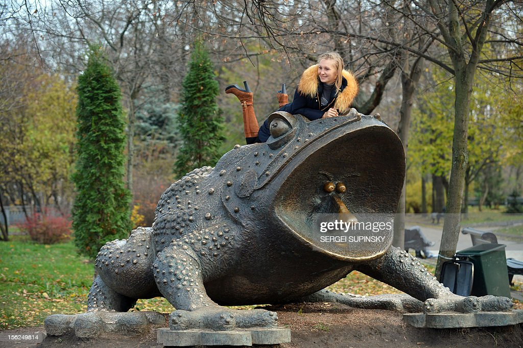 A girl poses for a picture on a park sculpture during a warm autumn day in the Ukrainian capital of Kiev on November 12, 2012. AFP PHOTO/ SERGEI SUPINSKY