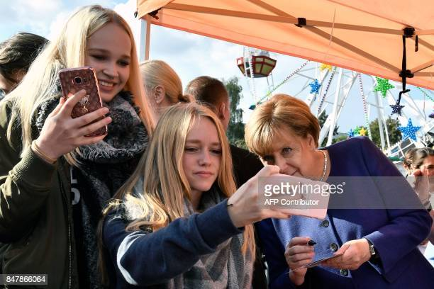 A girl poses for a selfie photo with German Chancellor Angela Merkel as she continued on the election campaign trail at a town fair in Stralsund on...