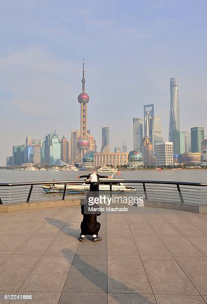 A girl poses for photos with the New Pudong Area the Financial Center of Shanghai with the Oriental Pearl TV Tower in the background on February 25...