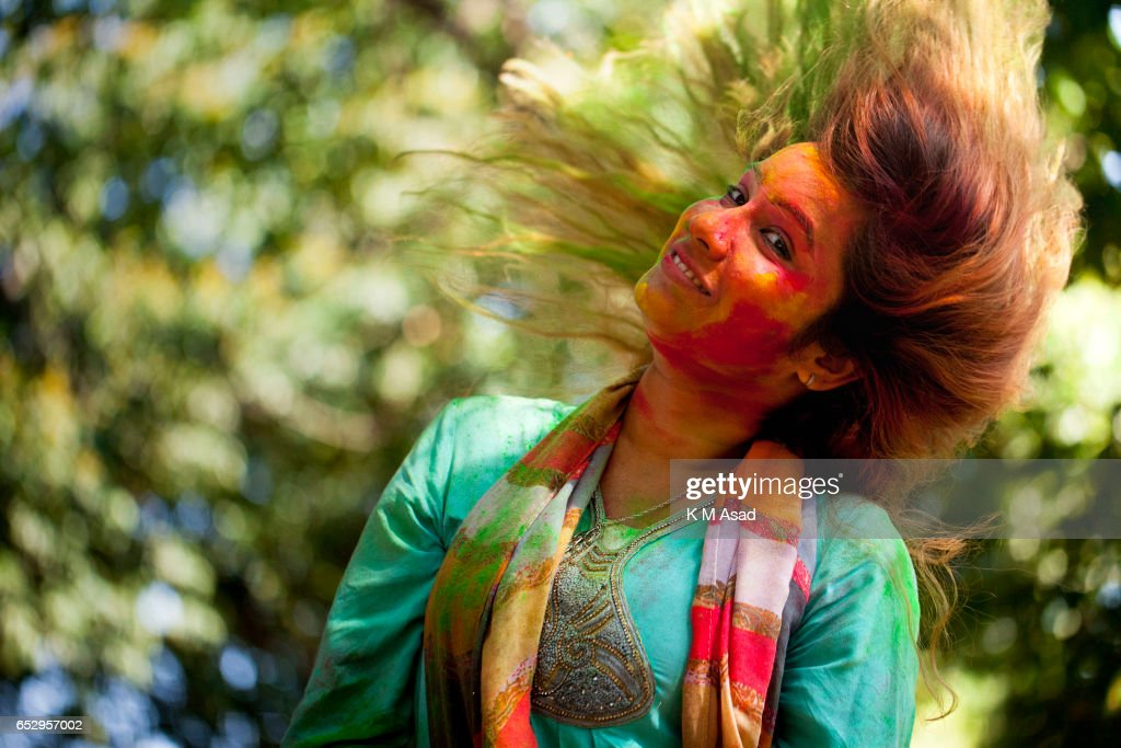 UNIVERCITY, DHAKA, BANGLADESH - : A girl poses for picture when she attends to celebrate the Holi Festival or Festival of Colors after smearing each other with colored powder in Dhaka, Bangladesh. Holi festival is celebrated on the full moon day in the month of Phalguna and marks the start of the spring season.