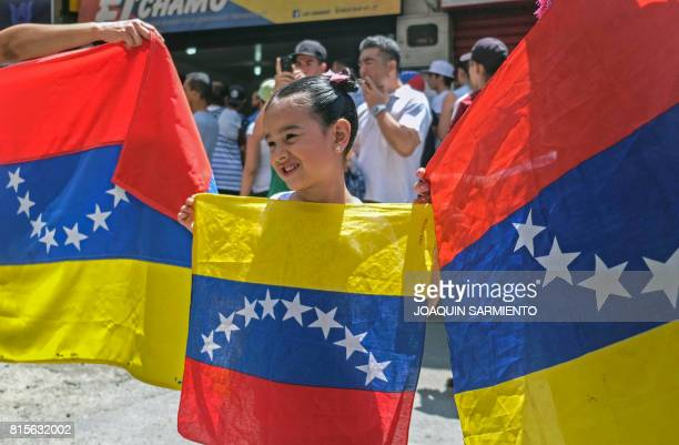 A girl poses for pictures holding a Venezuela's national flag as Venezuelans residing in Colombia queue at a polling station near Bolivar square in...