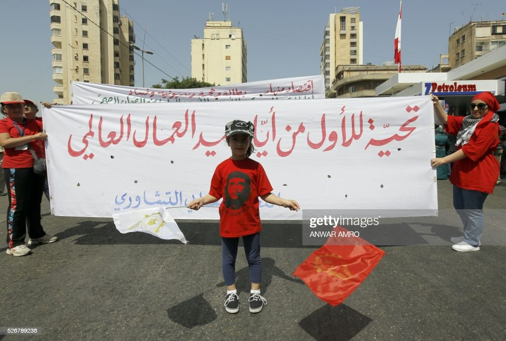 A girl poses in front of a banner as she takes part in a May Day rally organised by the Lebanese Communist party in Beirut on May 1, 2016. / AFP / ANWAR