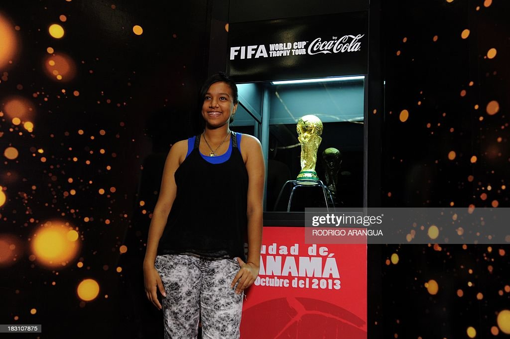 A girl poses next to the FIFA World Cup in Panama City, on October 4, 2013. The Cup is in Panama for two days as part of a tour to exhibit it in 89 countries before the beginning of the FIFA World Cup Brazil 2014. AFP PHOTO/ Rodrigo ARANGUA