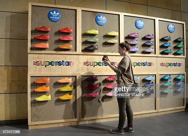 A girl poses with a shoe during the shareholders meeting of the German sporting goods company Adidas on May 7 2015 in Fuerth southern Germany AFP...