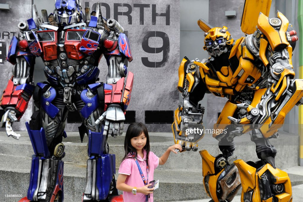 A girl poses with two Transformers robot on the launch day of the new amusement park ride at Universal Studios Singapore on December 3, 2011. 'Transformers: The Ride' is based on the Transformers movie franchise directed by Michael Bay.