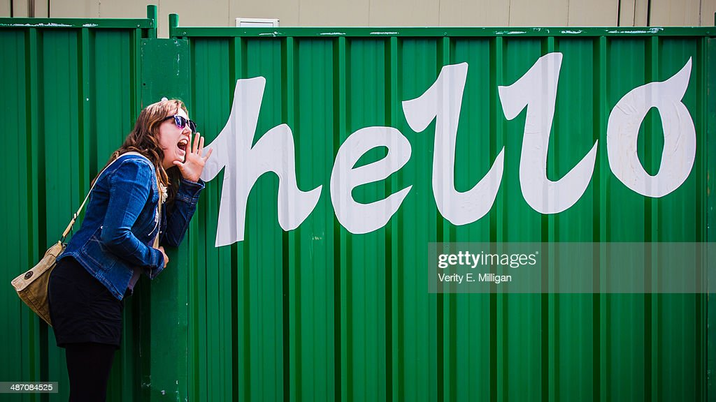 Girl posing next to 'Hello' sign on fence