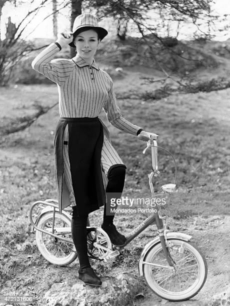 A girl posing on the saddle of a foldable Graziella bicycle made by the company Teodoro Carnielli 1965
