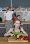 Girl posing while chopping vegetables