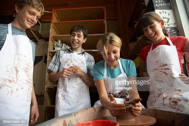 Girl (13-15) potting on wheel surrounded by classmates, smiling