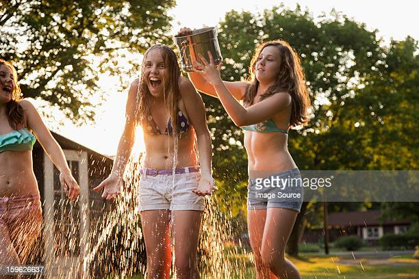 Girl pouring bucket of water over friend's head