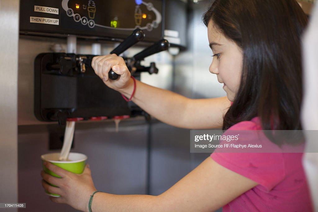 Girl pouring cup of frozen yogurt