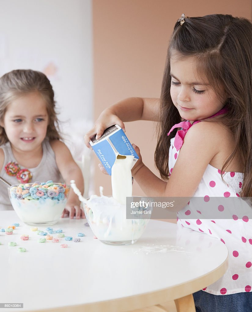 Girl pouring milk into cereal bowl : Stock Photo