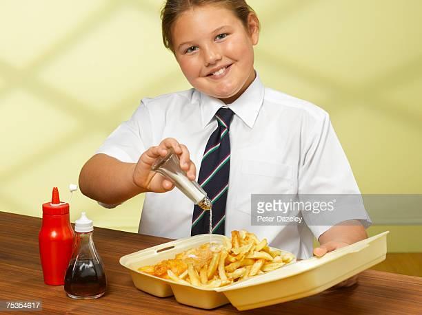 Girl (8-10) pouring salt on chips, smiling, portrait