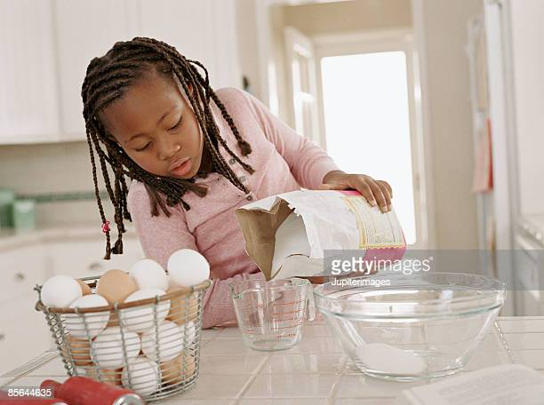 Girl pouring sugar into measuring cup