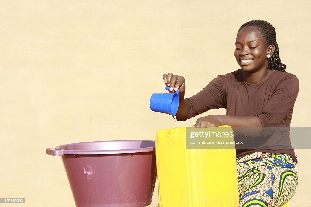 Girl pouring water in bucket : Stock Photo